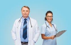 Усмехаясь доктора с доской сзажимом для бумаги и стетоскопами Стоковые Фото