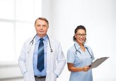 Усмехаясь доктора с доской сзажимом для бумаги и стетоскопами Стоковое Изображение