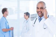 Усмехаясь доктор говоря на телефоне Стоковое Фото