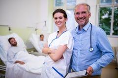 Усмехаясь доктор и медсестра стоя в палате стоковая фотография rf