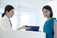 Усмехаясь доктор и пациент готовя счетчик в больнице смотря вниз на медицинской истории стоковое фото rf