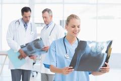 Усмехаясь доктор смотря рентгеновский снимок пока ее коллеги работают Стоковые Изображения