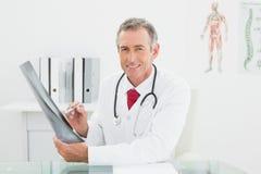 Усмехаясь доктор с изображением рентгеновского снимка легких в офисе Стоковые Фото
