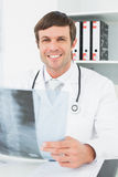 Усмехаясь доктор с изображением рентгеновского снимка позвоночника в медицинском офисе Стоковое фото RF
