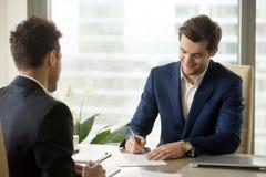 Усмехаясь документ подписания бизнесмена на встрече, кладя signatu Стоковая Фотография RF