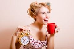 Усмехаясь домохозяйка с будильником и чашкой Стоковые Изображения