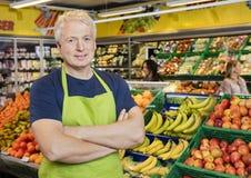 Усмехаясь оружия продавца стоящие пересеченные плодоовощами в магазине Стоковые Фото