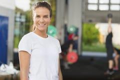 Усмехаясь остатки молодой женщины на спортзале фитнеса Стоковое фото RF