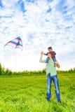 Усмехаясь отец держит ребенк и наблюдает змея в воздухе Стоковые Изображения
