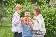 Усмехаясь отец и дети есть свежие овощи в папа †природы «счастливый держа красочные перцы отрезанный в форме французского карто стоковые фотографии rf