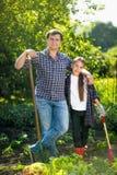 Усмехаясь отец и дочь представляя на саде с лопаткоулавливателями Стоковые Фото