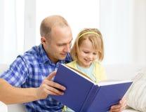 Усмехаясь отец и дочь с книгой дома стоковые изображения rf