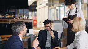 Усмехаясь официантка принимая заказ от группы в составе предприниматели во время бизнес-ланча видеоматериал