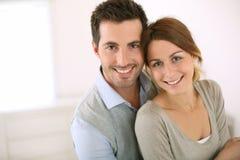 Усмехаясь один другого обнимать пар дома стоковая фотография rf