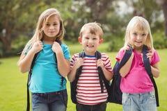Усмехаясь одноклассники с schoolbags Стоковые Фотографии RF