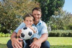 Усмехаясь папа и сын в парке Стоковые Изображения