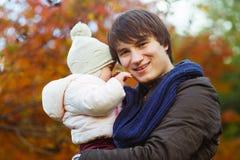 Усмехаясь папа с дочерью в руках на деревьях предпосылки осени стоковая фотография rf
