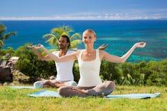 Усмехаясь пара делая йогу работает outdoors Стоковая Фотография RF