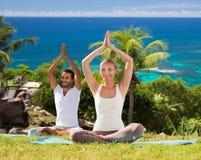 Усмехаясь пара делая йогу работает outdoors Стоковое фото RF