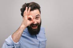 Усмехаясь парень показывая О'КЕЫ жест на камере стоковые изображения rf