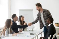 Усмехаясь партнер бизнесмена приветствующий новый на групповой встрече с Стоковое Изображение
