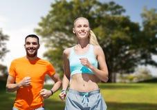 Усмехаясь пары бежать над предпосылкой парка лета Стоковые Фотографии RF