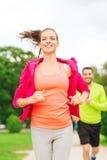 Усмехаясь пары бежать outdoors Стоковое Изображение
