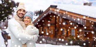 Усмехаясь пары в одеждах зимы обнимая outdoors Стоковая Фотография
