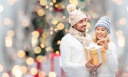 Усмехаясь пары в одеждах зимы с подарочной коробкой Стоковое Изображение