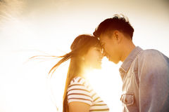 Усмехаясь пары влюбленн в предпосылка солнечного света Стоковое Изображение