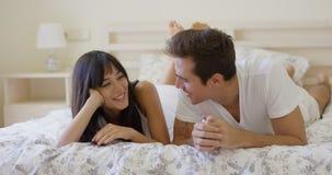 Усмехаясь пары говоря пока кладущ вниз на кровать Стоковое Изображение RF