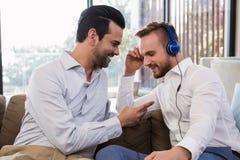 Усмехаясь пары гомосексуалиста ослабляя в живущей комнате Стоковая Фотография RF