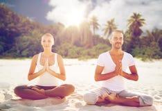 Усмехаясь пары делая тренировки йоги на пляже Стоковые Фото