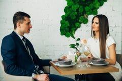 Усмехаясь пары имея обедающий и выпивая белое вино на дате в ресторане Стоковое Изображение