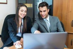 Усмехаясь пары используя портативный компьютер Стоковая Фотография RF
