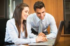 Усмехаясь пары используя портативный компьютер Стоковые Фотографии RF