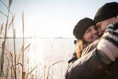 Усмехаясь пары обнимая в лесе зимы стоковые изображения rf