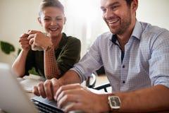 Усмехаясь пары дома используя компьтер-книжку Стоковая Фотография RF
