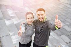 Усмехаясь пары показывая большие пальцы руки вверх на улице города стоковая фотография rf
