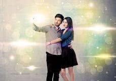 Усмехаясь пары принимая selfie в свете яркого блеска Стоковое Фото