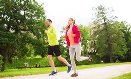 Усмехаясь пары при наушники бежать outdoors Стоковые Изображения