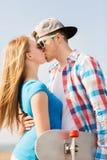 Усмехаясь пары при скейтборд целуя outdoors Стоковая Фотография