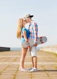 Усмехаясь пары при скейтборд целуя outdoors Стоковое Изображение RF