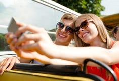 Усмехаясь пары при smartphone делая selfie Стоковые Изображения
