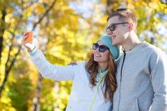 Усмехаясь пары при smartphone принимая selfie Стоковая Фотография RF