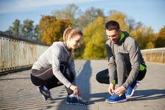 Усмехаясь пары связывая шнурки outdoors Стоковая Фотография