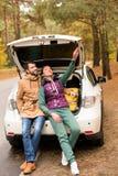 Усмехаясь пары сидя в багажнике автомобиля Стоковые Фото