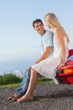 Усмехаясь пары сидя на их клобуке автомобиля cabriolet Стоковое Изображение RF