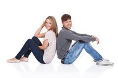 Усмехаясь пары сидя спина к спине Стоковые Фотографии RF