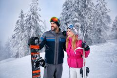 Усмехаясь пары совместно катаясь на лыжах на снежной горе и смотреть сома Стоковое Фото